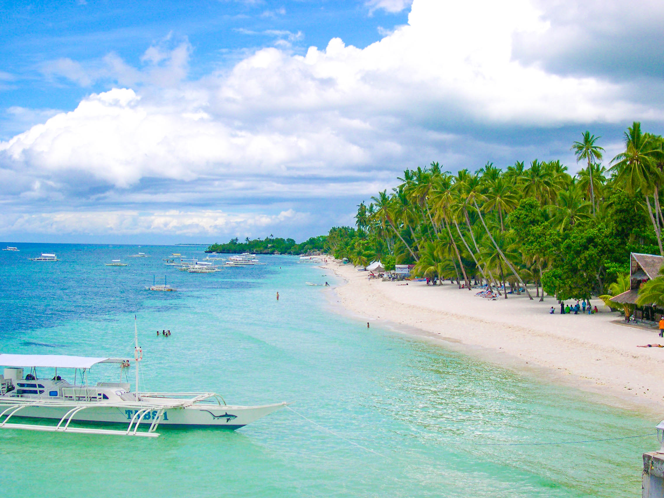 White sand beach with coconut palms fronting clear waters with boats in anchor in Panglao, one of the most amazing places to visit in the Philippines