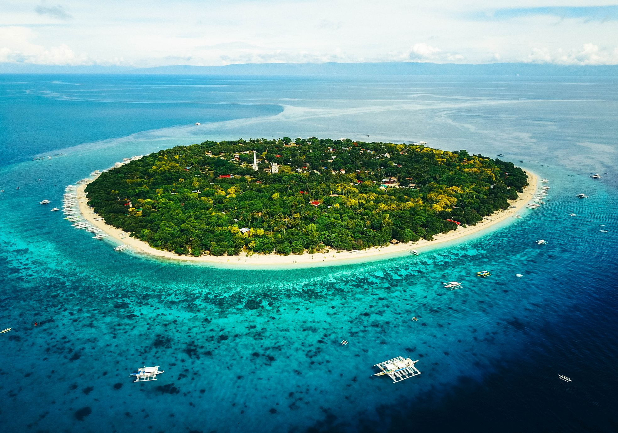 Aerial view of an island fringed with a white sandy shoreline with a coconut palm forest in the middle amidst blue and turquoise waters in Panglao, Philippines