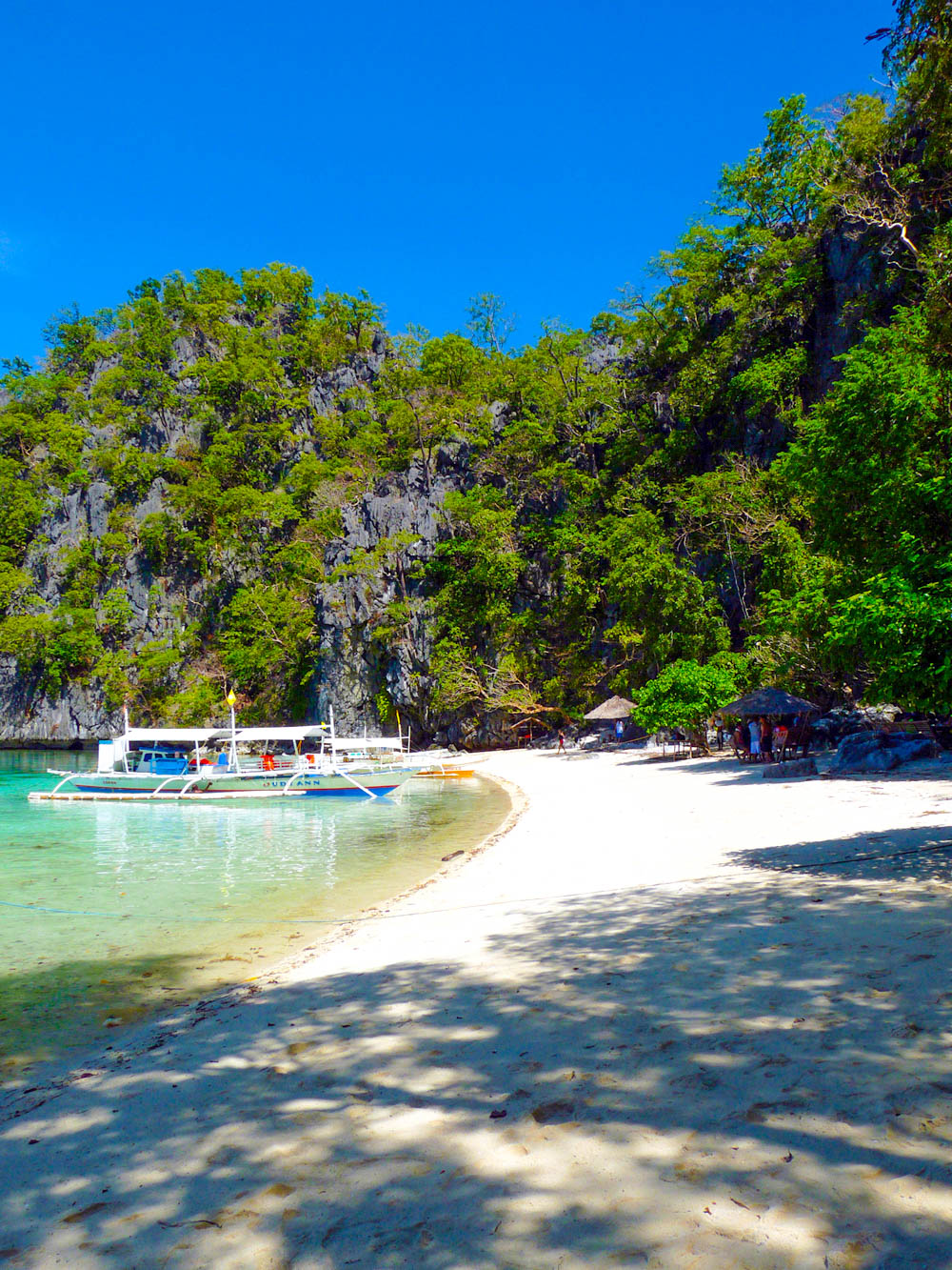 Outrigger boat near a white sand beach backed by limestone cliffs overhung with vegetation in Coron, Philippines