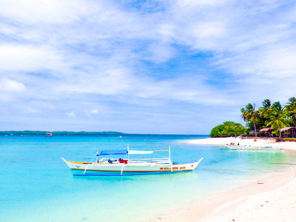 Boat moored on blue and cerulean waters before a white sand beach with coconut palms in the distance in Bantayan Island, Philippines