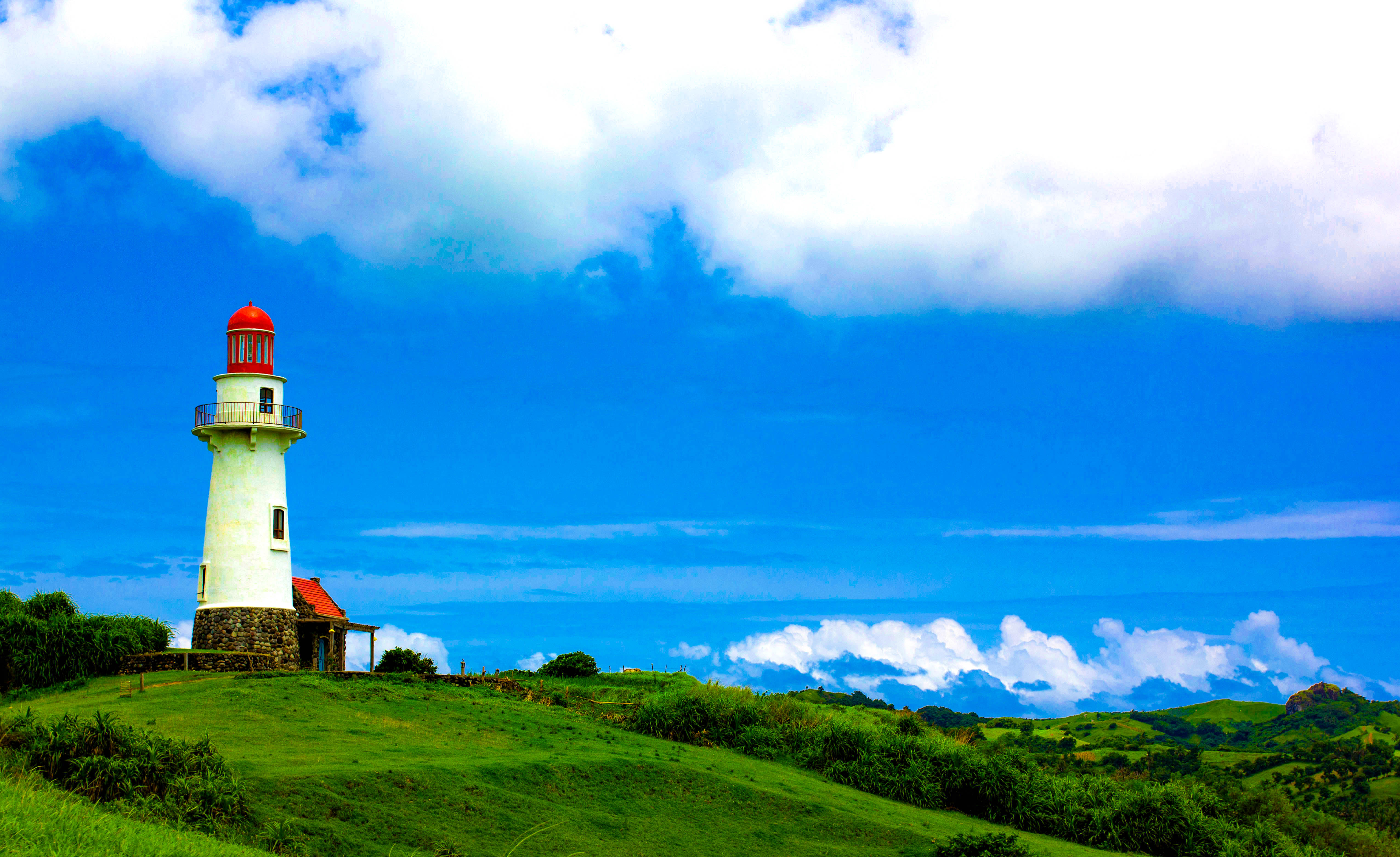 Lone lighthouse stands upon a green hilly land beneath a blue sky with clouds in Batanes, Philippines