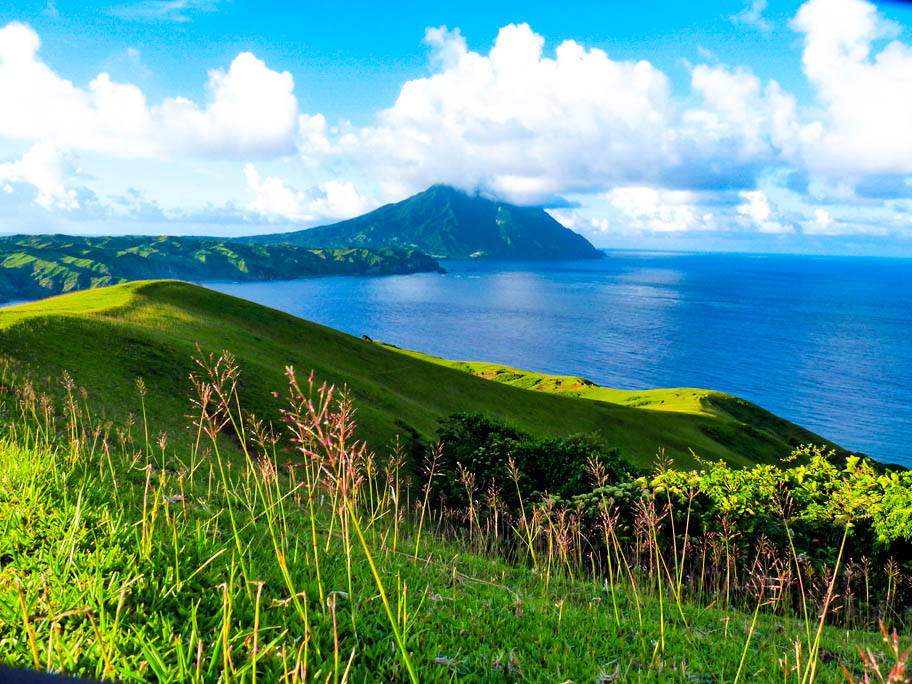Grassy rolling hills overlooking the sea with a tall mountain wreathed in clouds looming in the distance in Batanes, Philippines