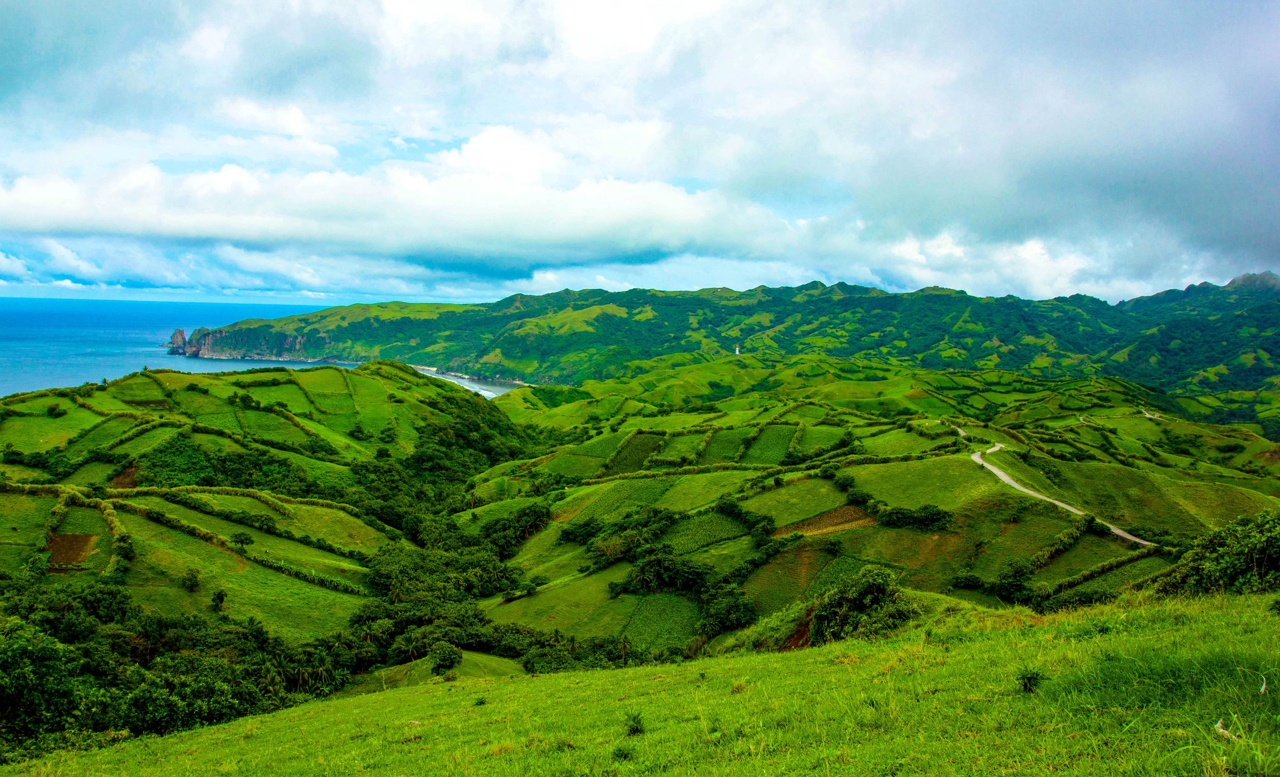 Rolling green hills beside the sea beneath a cloudy sky in Batanes, Philippines