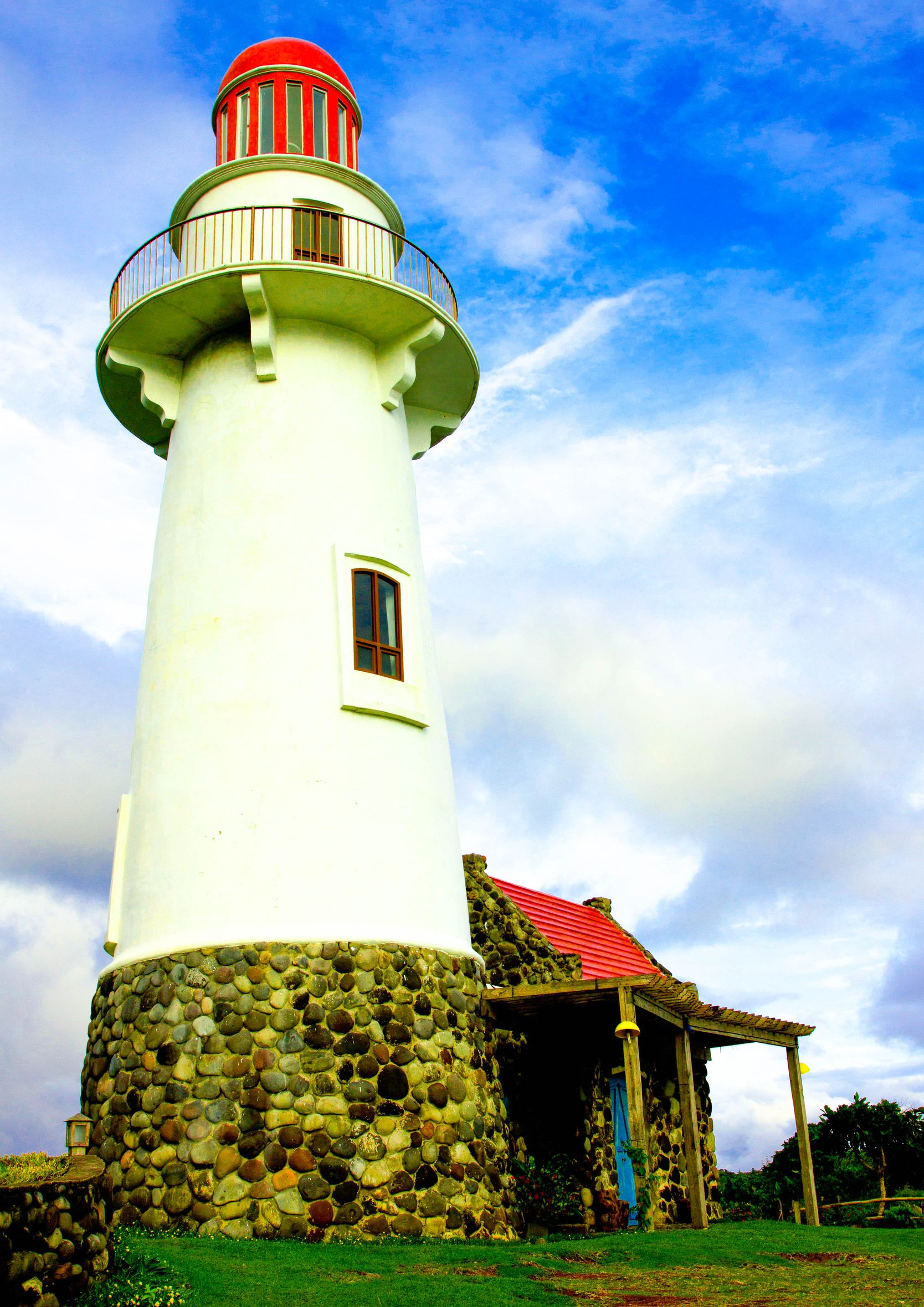 White lighthouse raised on a green hill beneath a cloudy sky