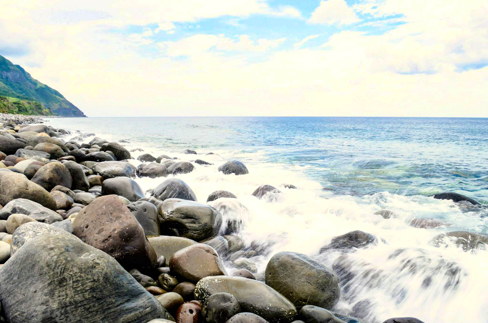 White waves wash over a shore of boulders in Batanes, Philippines
