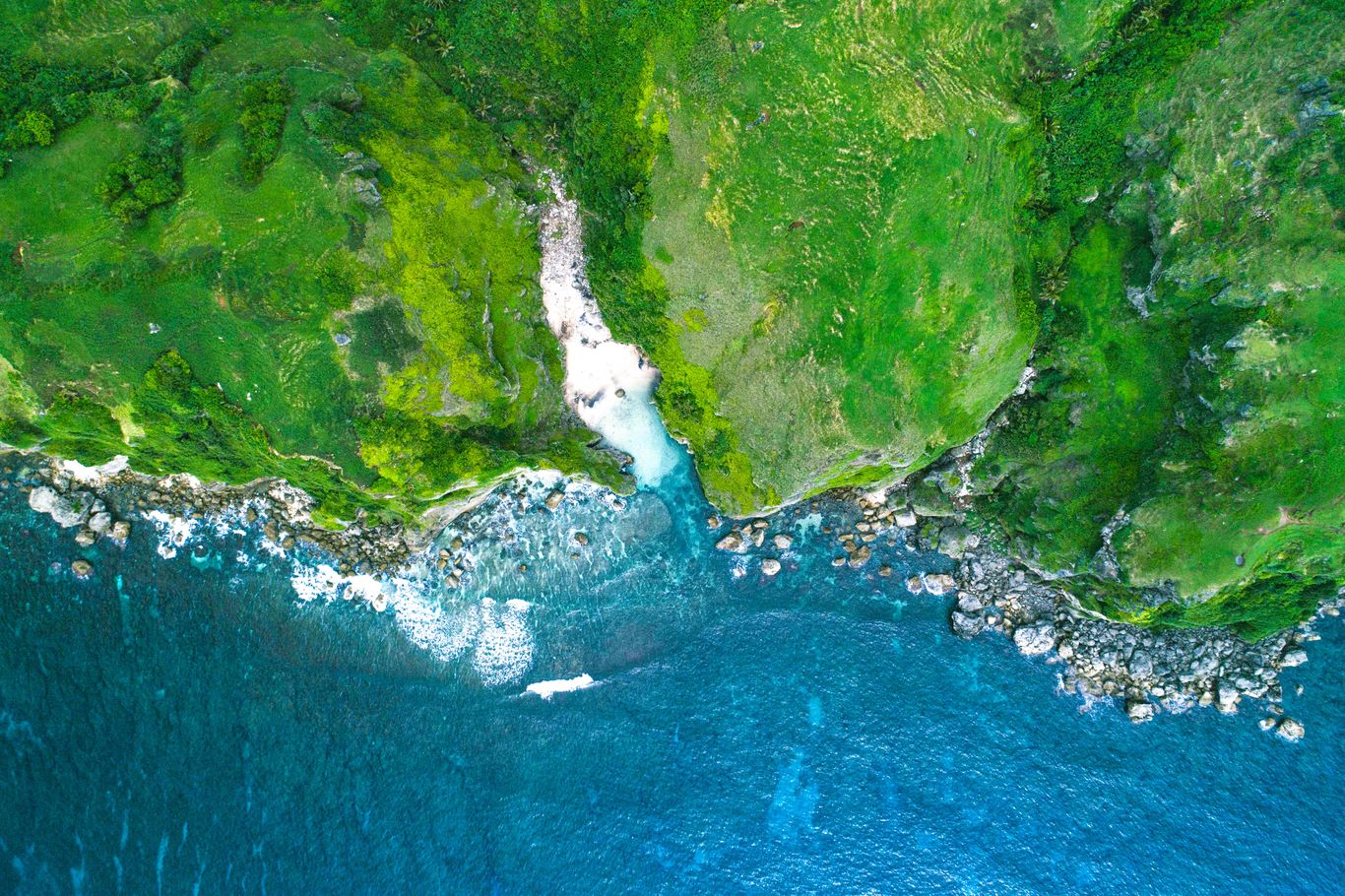 Aerial view of green cliffs beside the sea in Batanes, Philippines