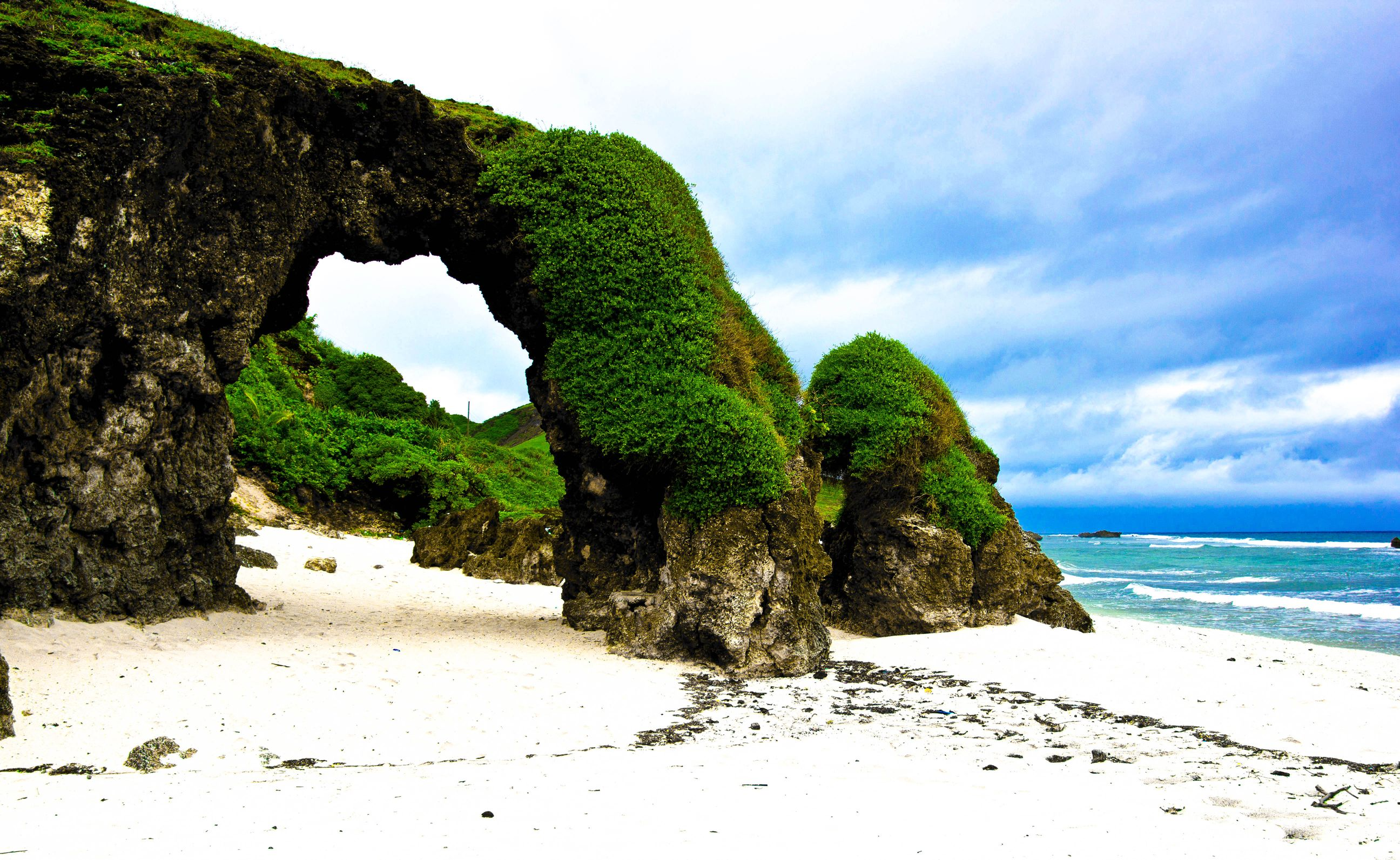 Stone arch covered in moss stands upon a white sand beach in Batanes, Philippines