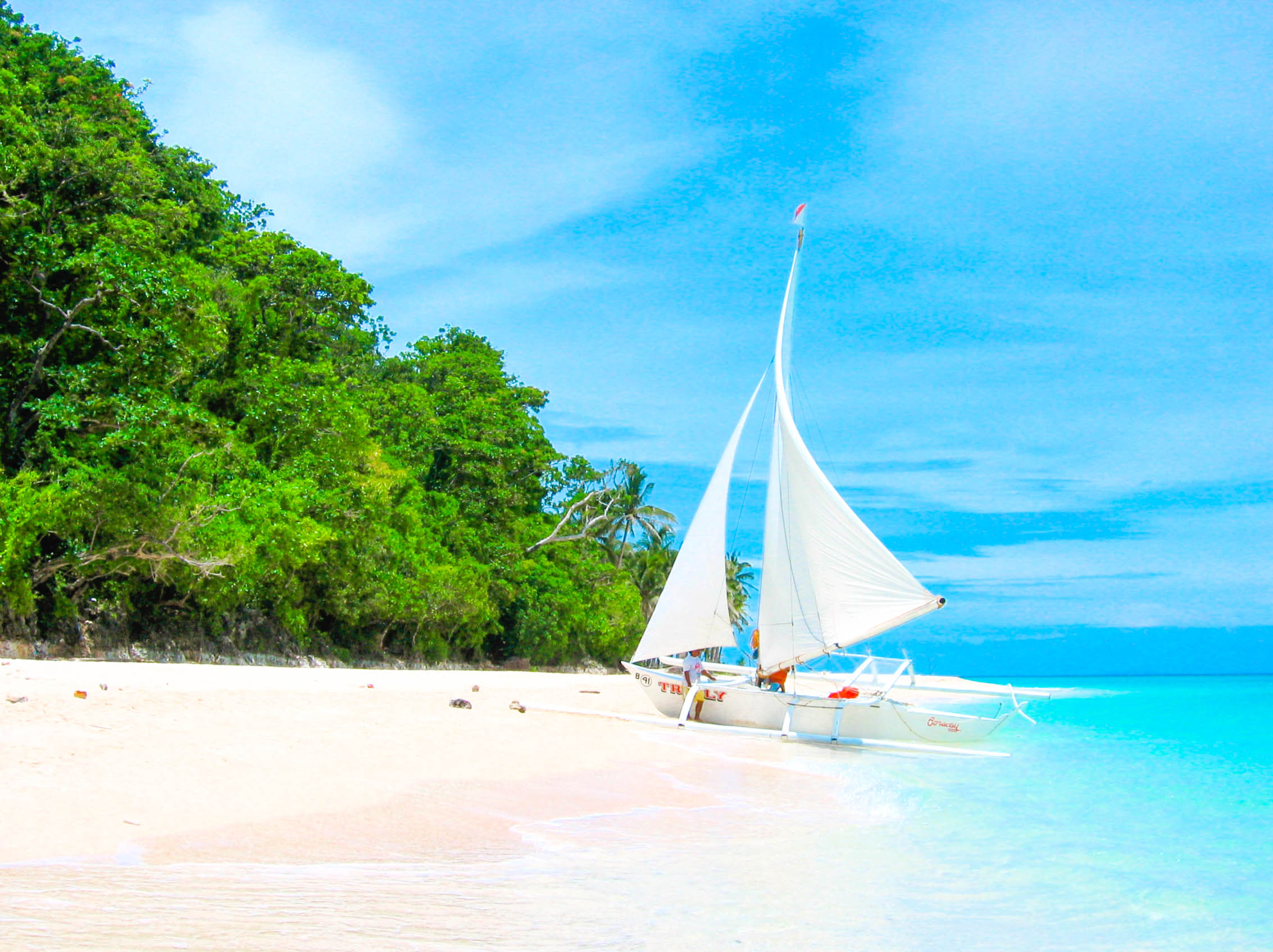 Small white sailboat moored on a white sand beach with green trees under a blue sky in Boracay, Philippines
