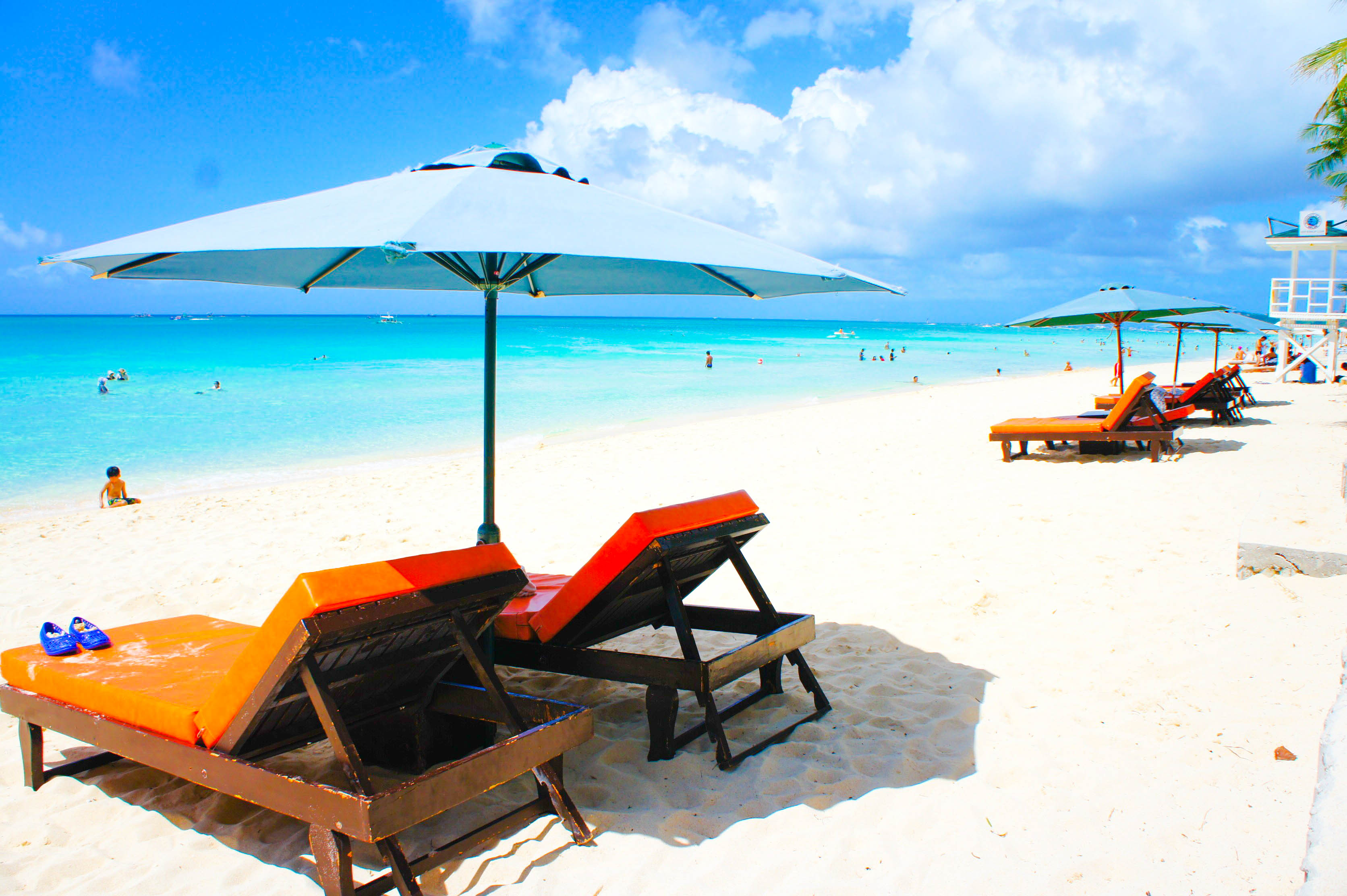 Beach chairs with umbrella on a white sand beach fronting blue waters