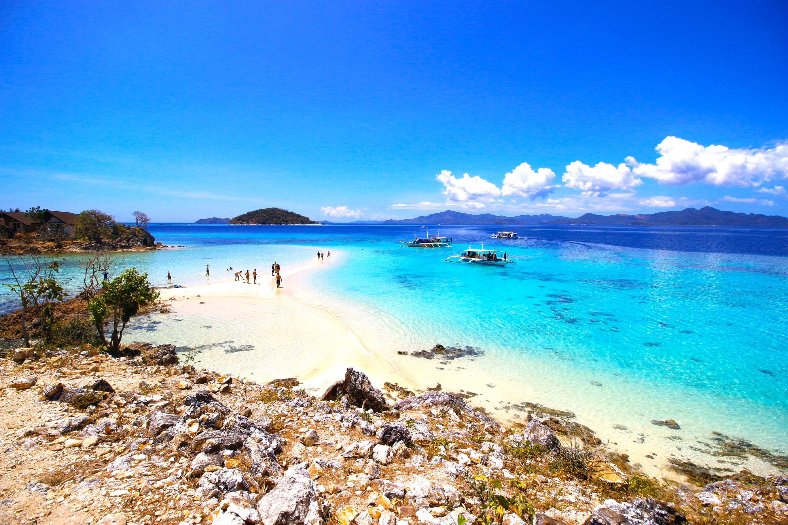 Patches of rocks overlooking a white sand beach surrounded by crystal clear waters with several boats in anchor in Coron, one of the most amazing places to visit in the Philippines