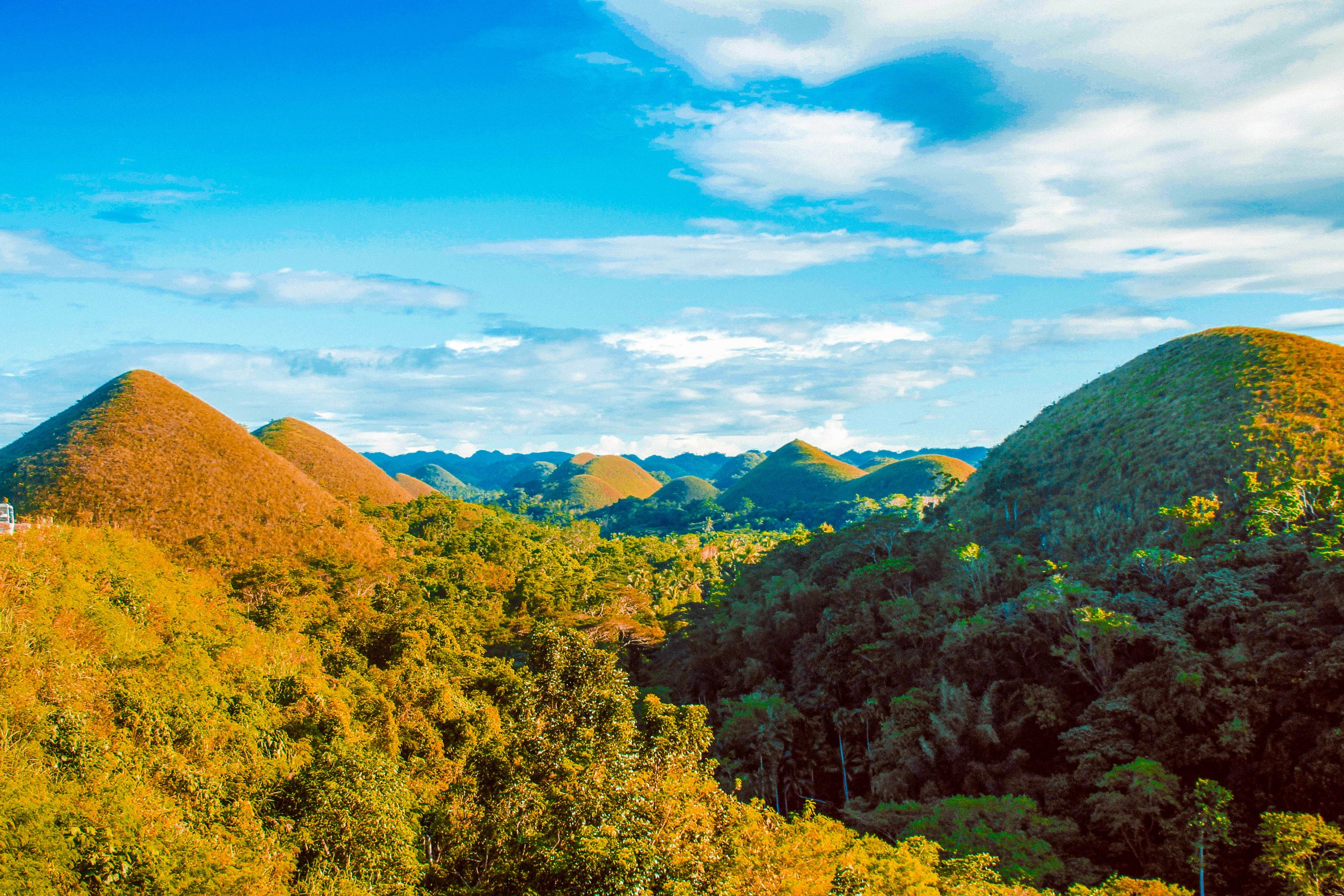 Numerous brown hills rising above green forests in Bohol, Philippines