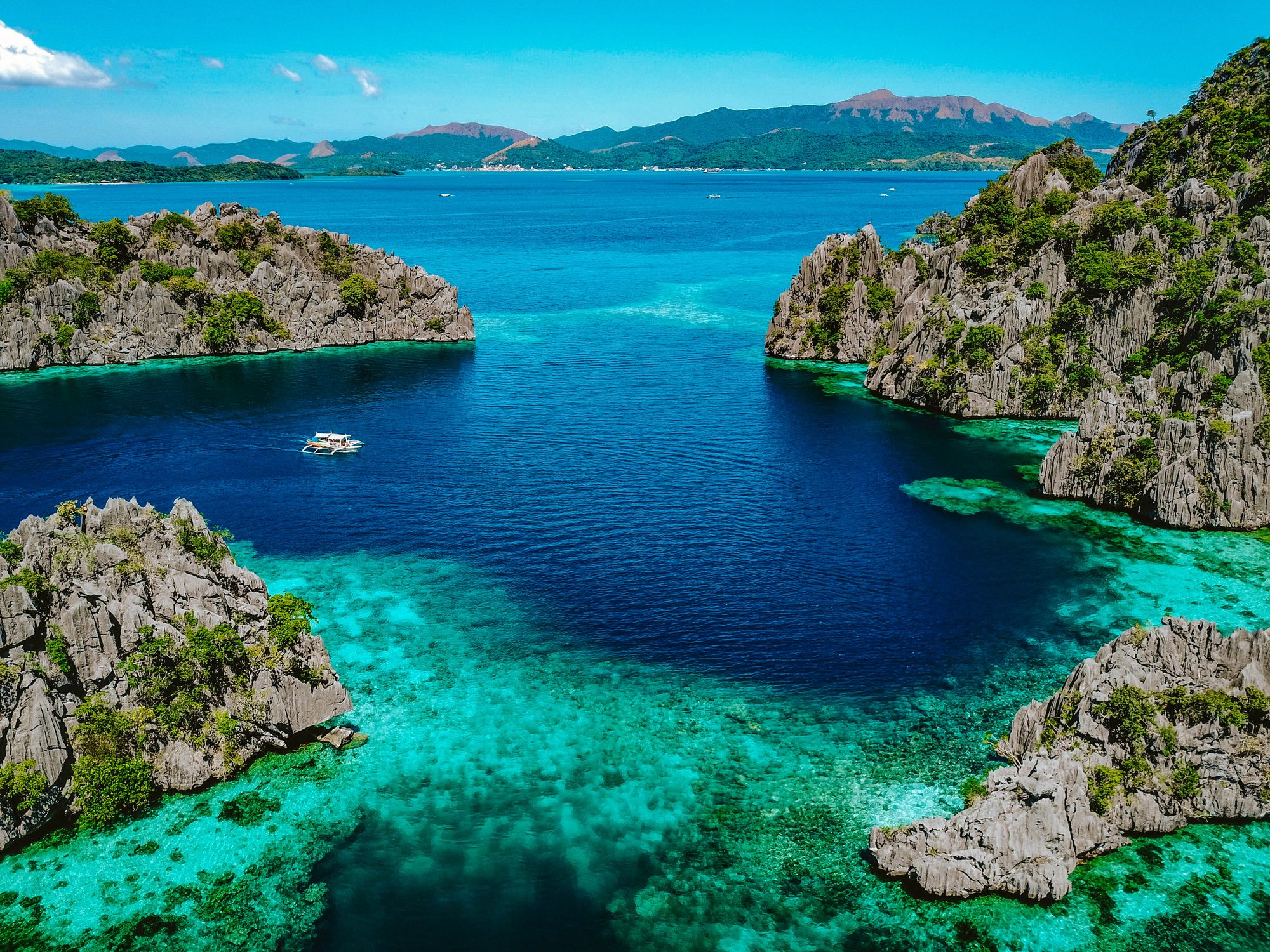 Small outrigger boat sails through a blue bay surrounded by limestone cliffs in Coron, Palawan, Philippines