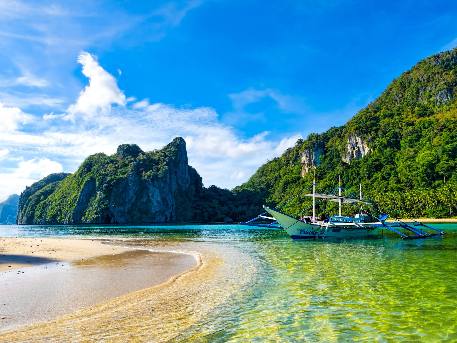 Boat moored close to shore fronting crystalline waters with limestone cliffs clad with vegetation in the distance in El Nido, Palawan, Philippines