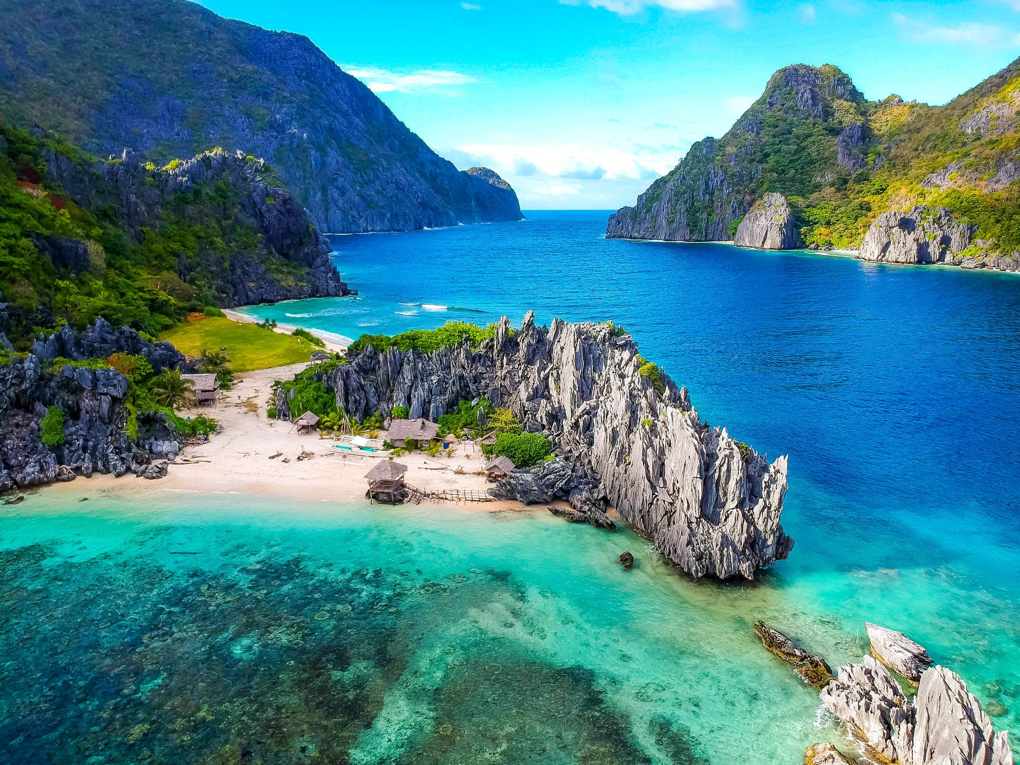 Aerial view of islands with white sand beaches, limestone cliffs, green mountains amidst blue and turquoise waters in El Nido, Palawan, Philippines