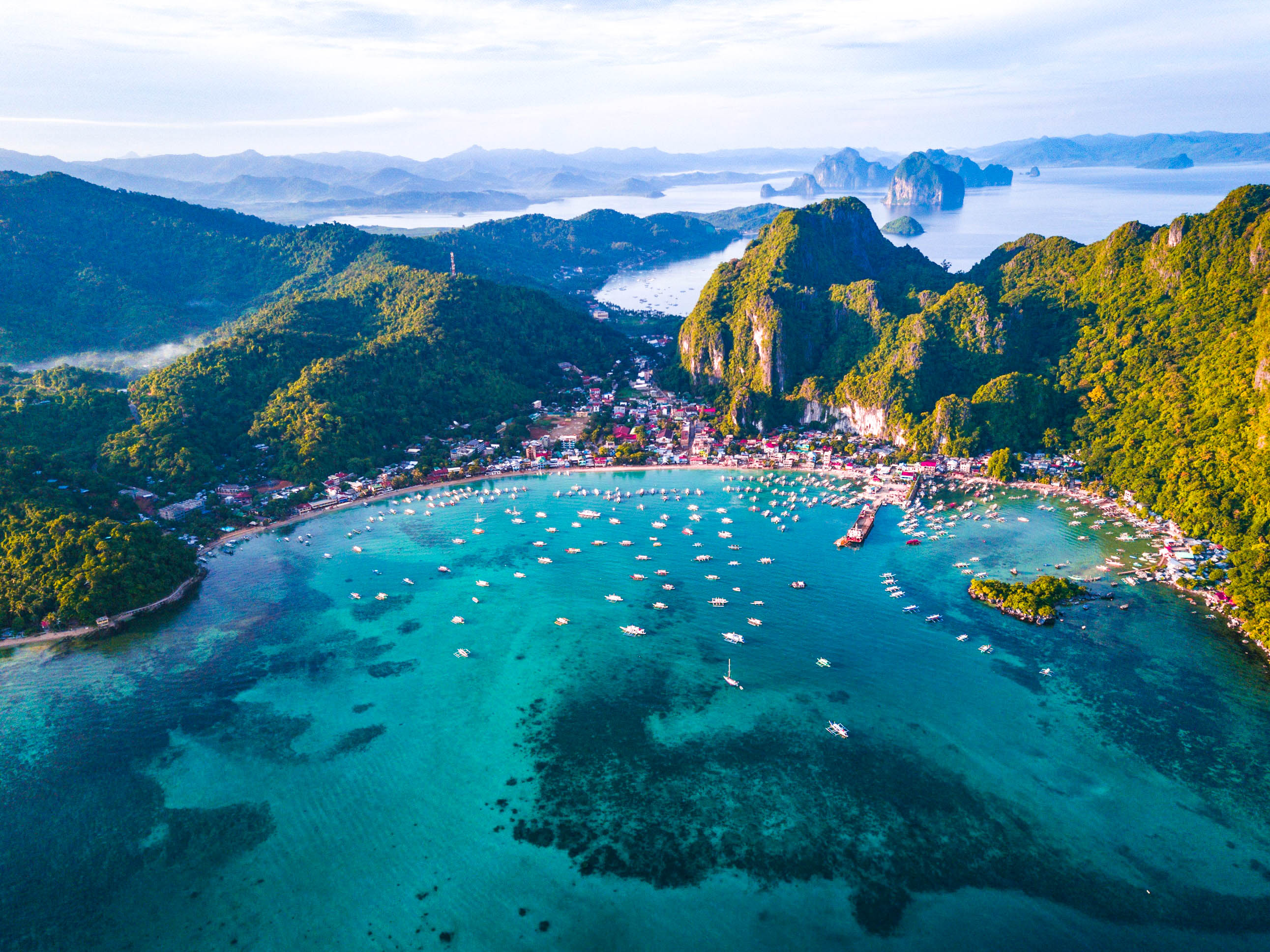 Aerial view of a town nestled between towering mountains and a sheltered bay filled with numerous outrigger boats in El Nido, Palawan, Philippines