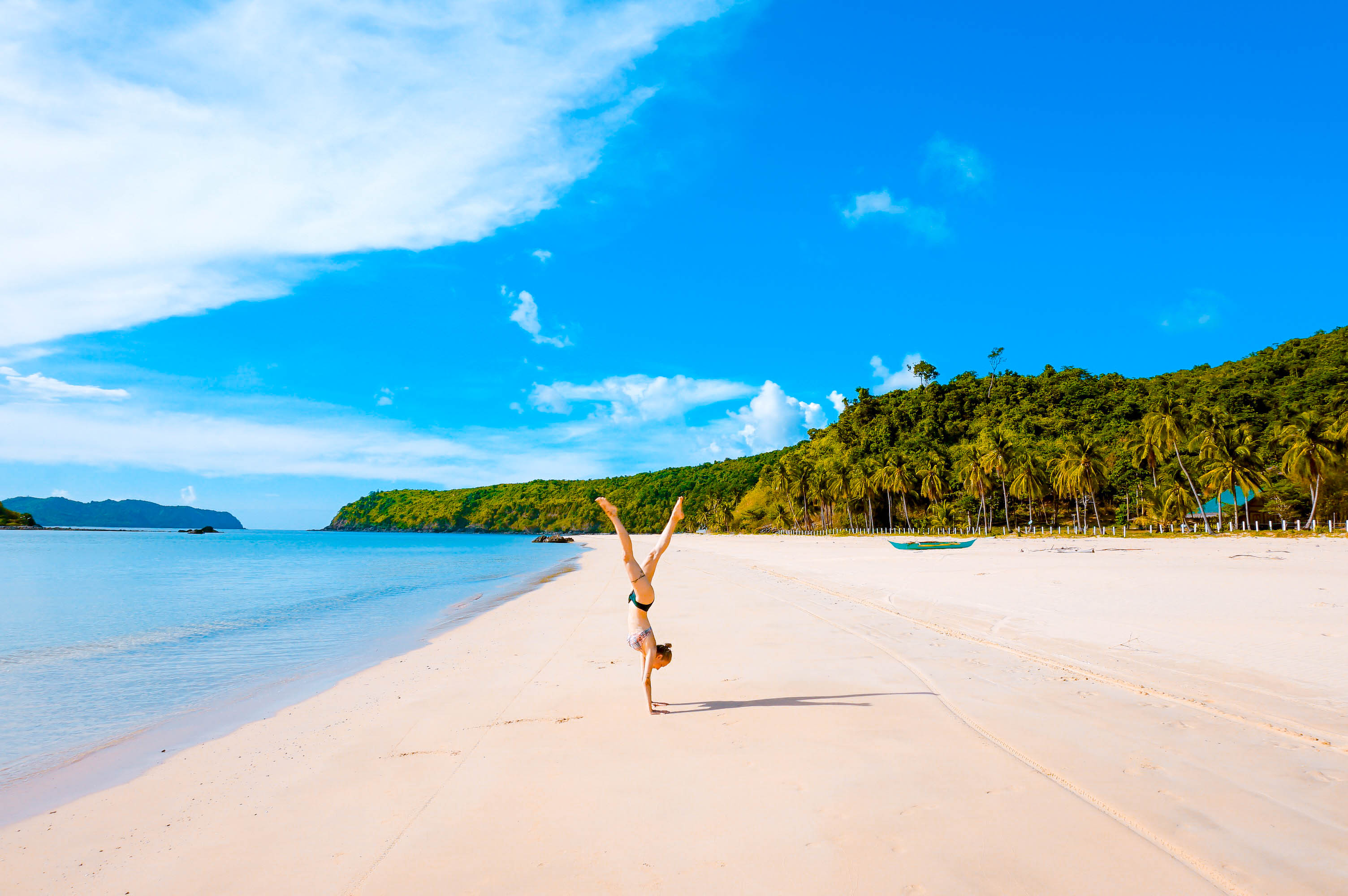 Woman in bikini doing a handstand on a white sand beach with coconut palm forests in the distance in El Nido, Palawan, Philippines