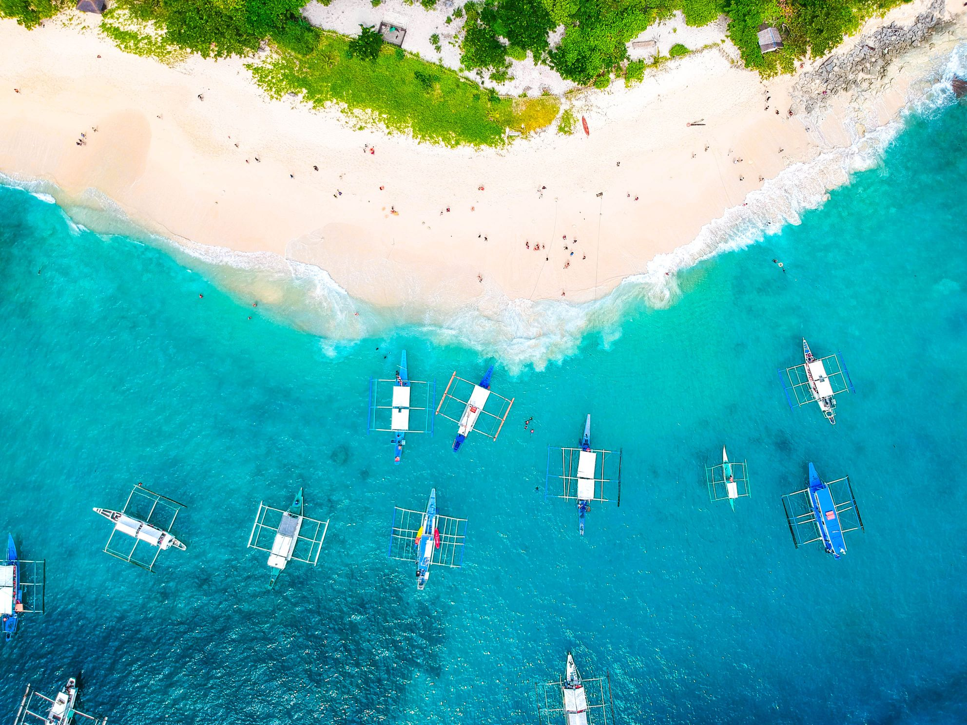 Aerial view of numerous outrigger boats moored on crystalline turquoise waters before a white sand beach in El Nido, Palawan, Philippines