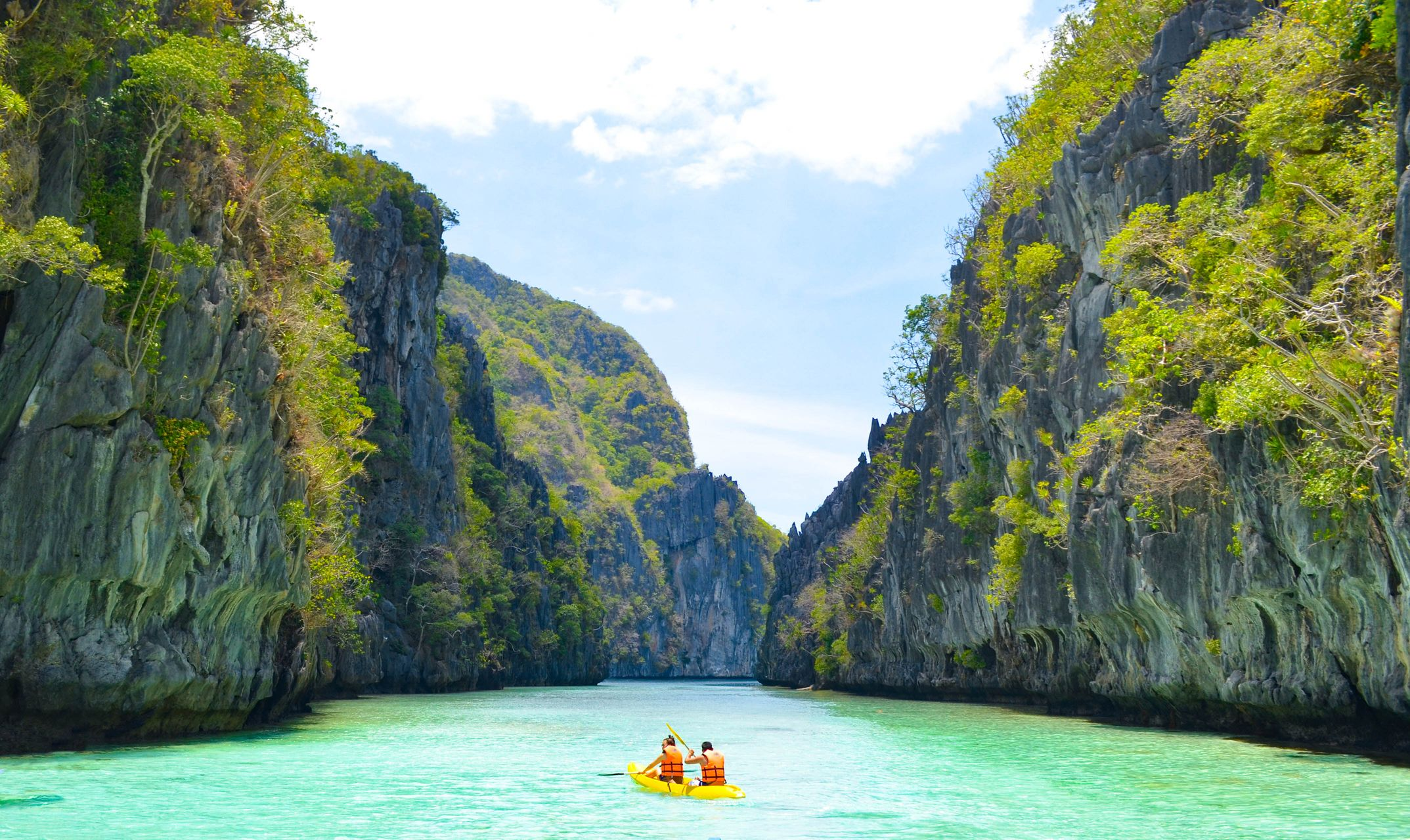 Two people row an small boat through jade waters flanked by towering limestone cliffs in El Nido, Palawan, Philippines