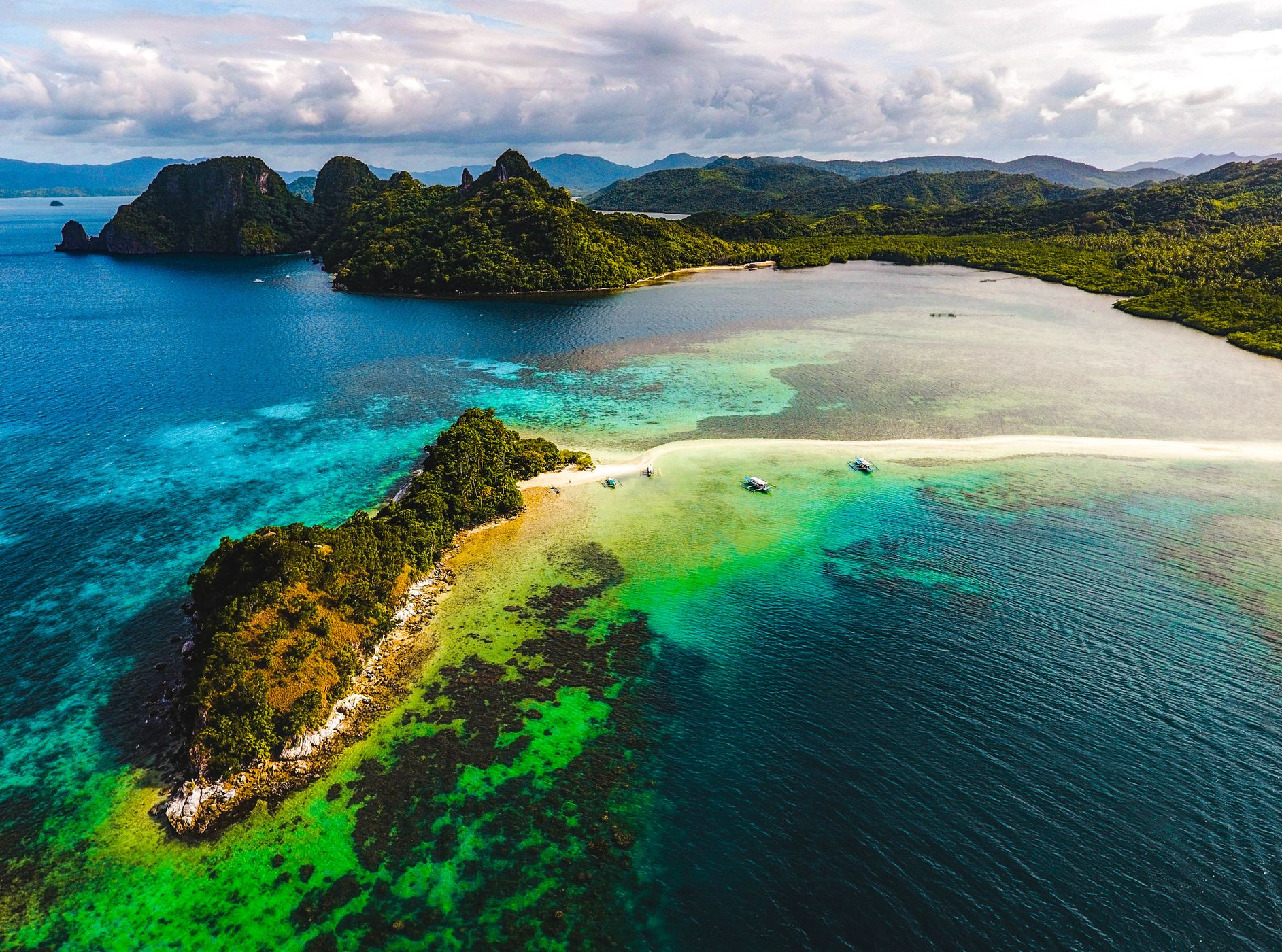 Aerial view of a small island connected to the mainland by a shining white sand bar in El Nido, Palawan, Philippines