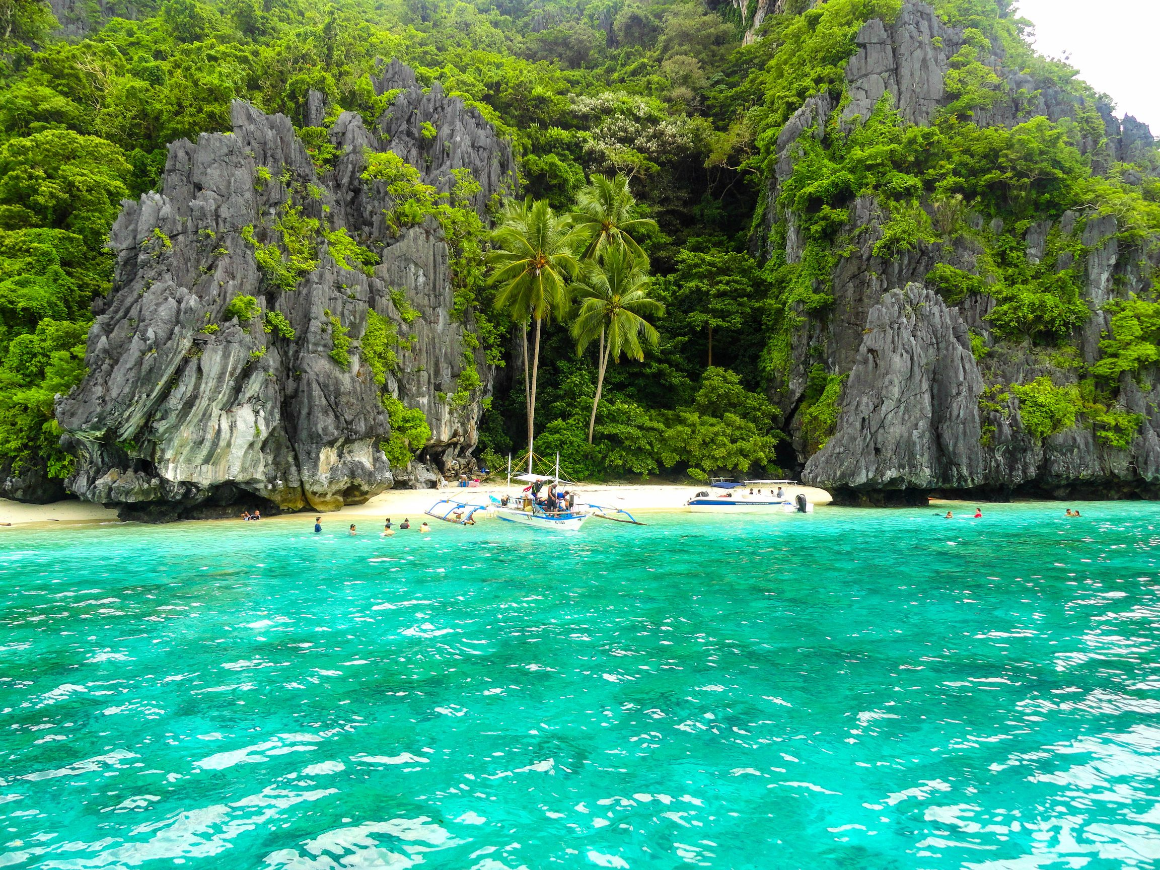 A white sand beach bounded between crystal clear turquoise waters and limestone cliffs clad with vegetation in El Nido, Palawan