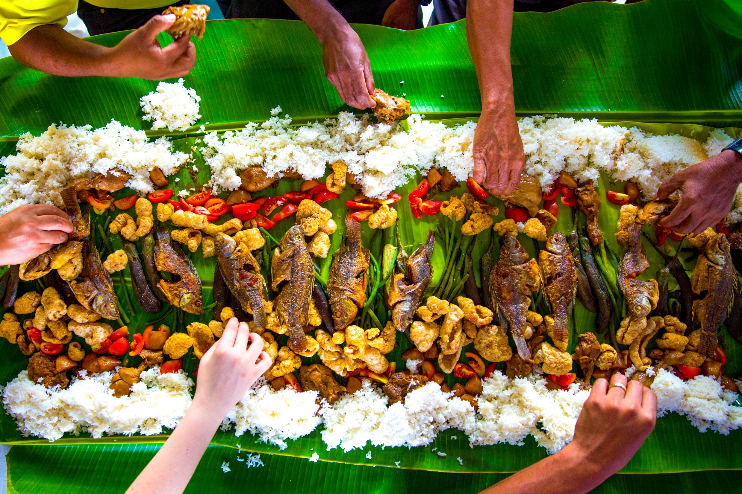 top view of hands getting food from a banquet laid out on banana leaves in a traditional Filipino 'boodle'