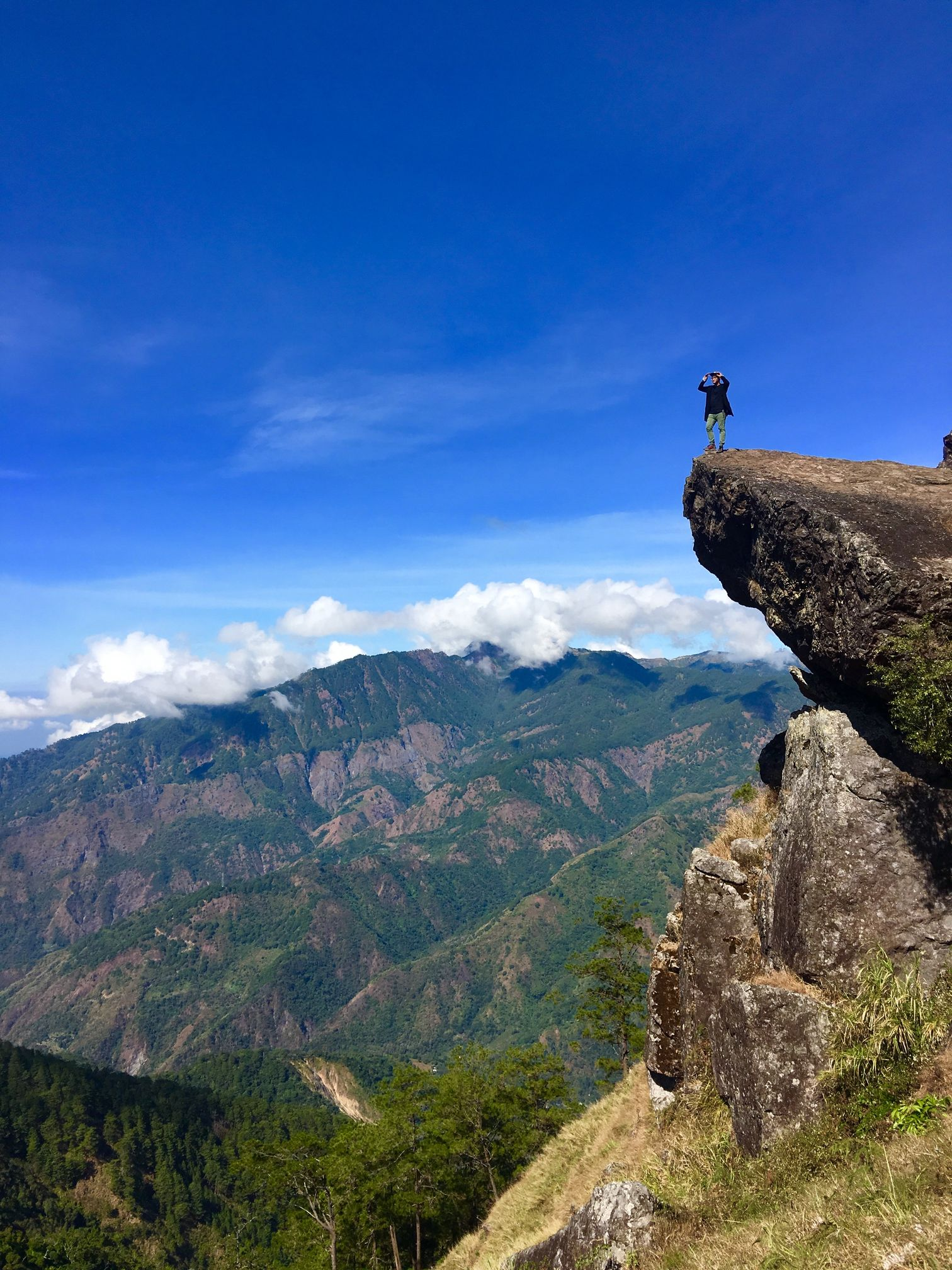 Man poses at the Gungal Rock overlooking the Cordilleras in Mount Ulap