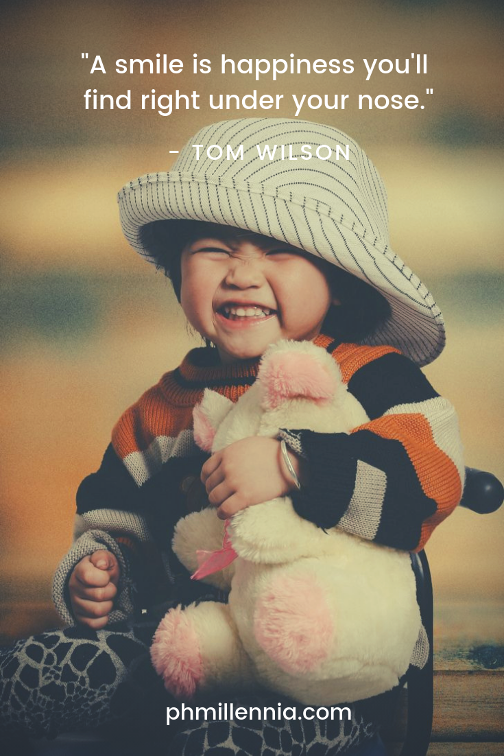 An adorable kid wearing a hat and hugging a plushy smiles and laughs for the camera.