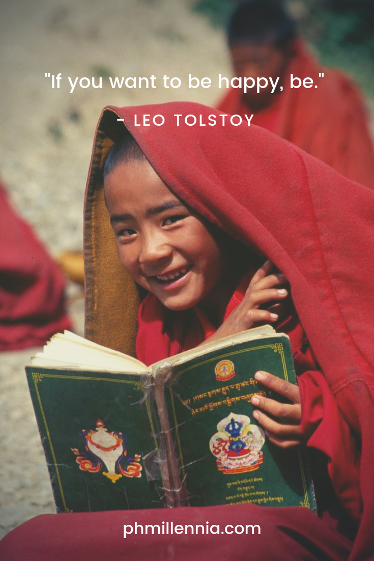 An Asian kid training to be a monk smiles for the camera in happiness while reading a book.