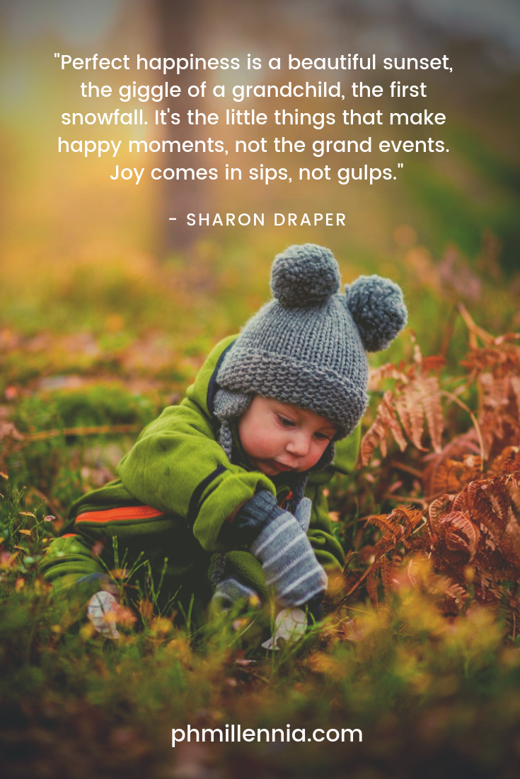 A quote on happiness by Sharon Drapes on a background of a child playing amongst the grass.