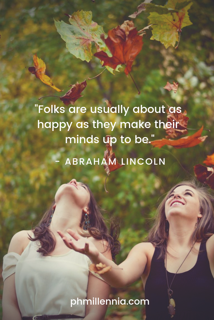 Two female friends celebrate happiness and friendship by throwing autumn leaves into the air.