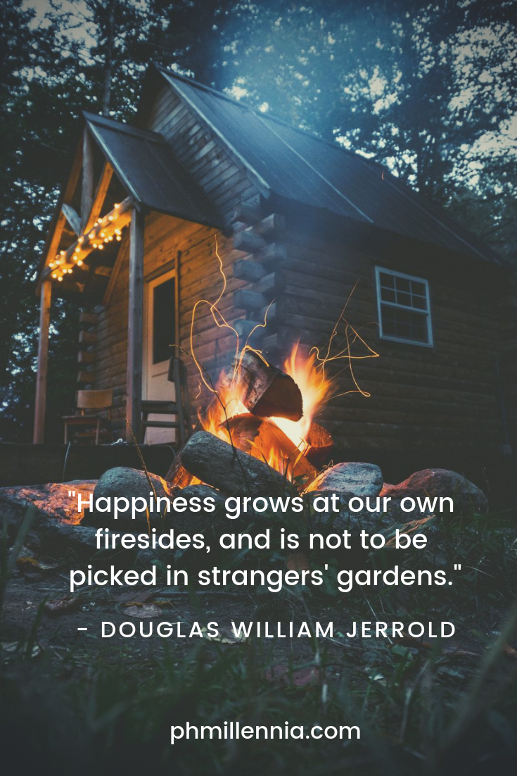 A quote on happiness by Douglas WIlliam Jerrold on a background of a campfire before a log cabin.