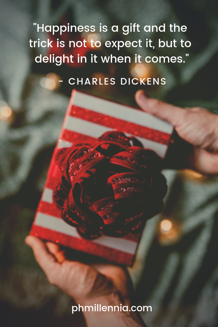 A quote on happiness by Charles Dickens on a background of a pair of hands holding a wrapped present.
