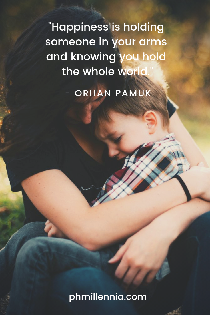 A quote on happiness by Orhan Pamux on a background of a mother holding her son in a tight embrace.