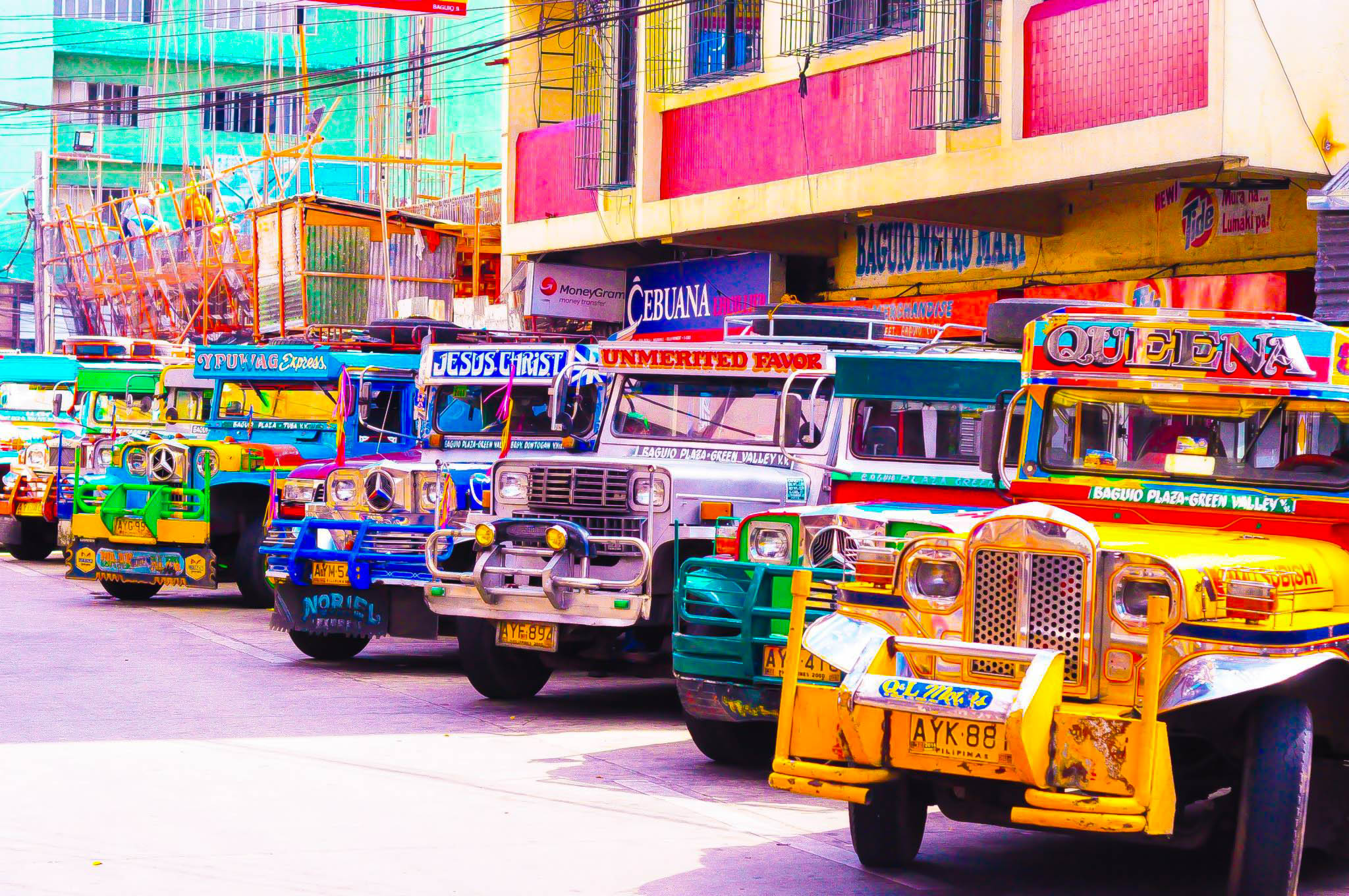 Array of colorful jeepneys parked before buildings