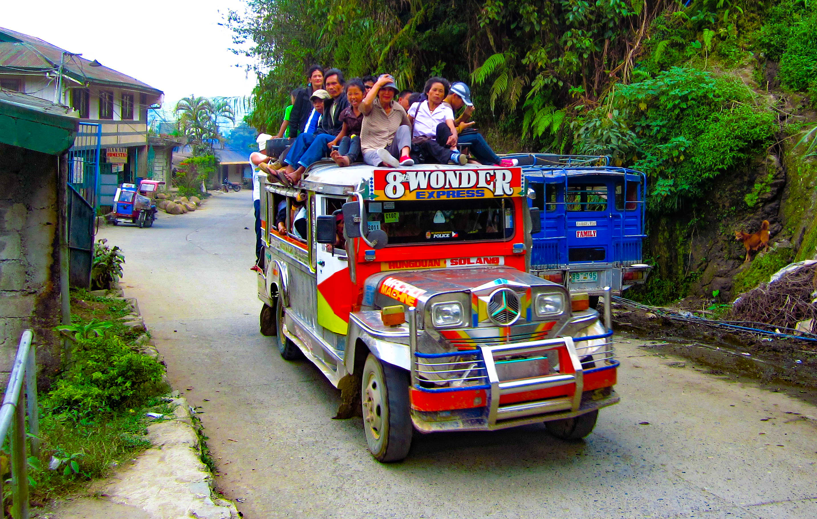 Jeepney overloaded with passengers within and without passing along