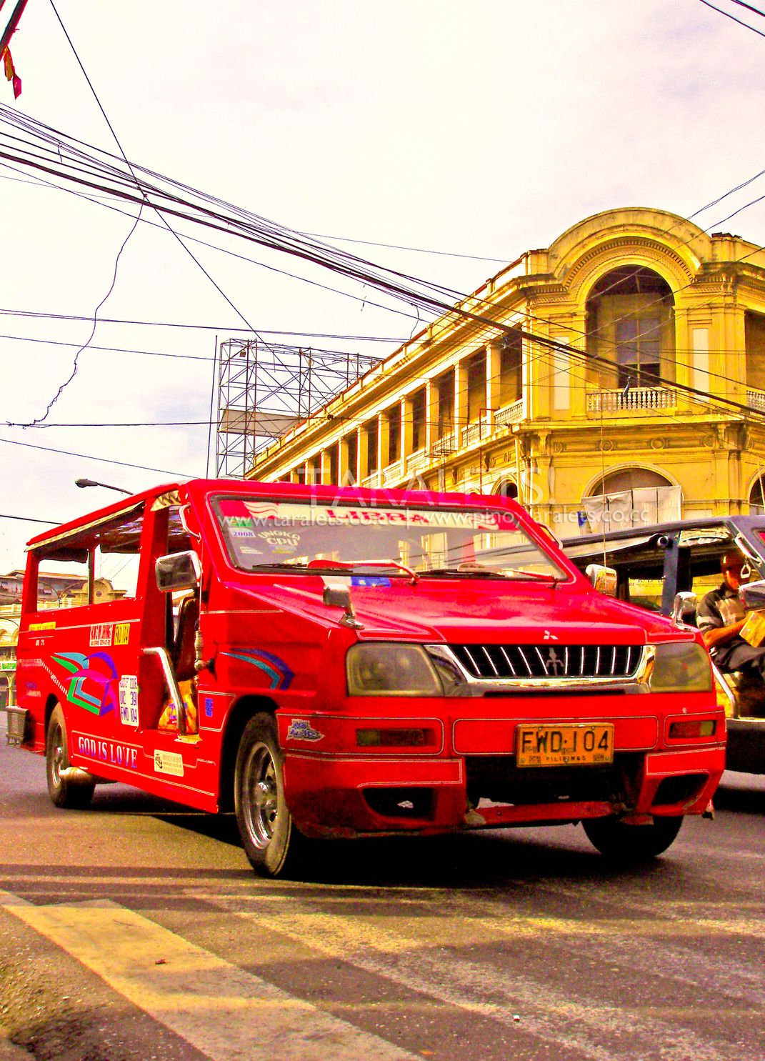Red jeepney passing along