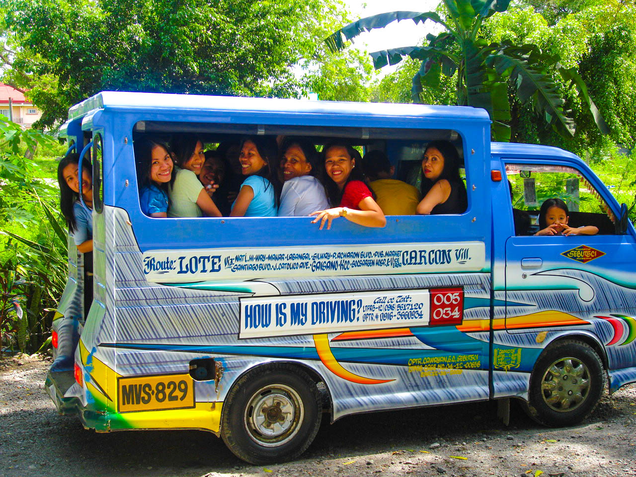 Jeepney filled with passengers passing along