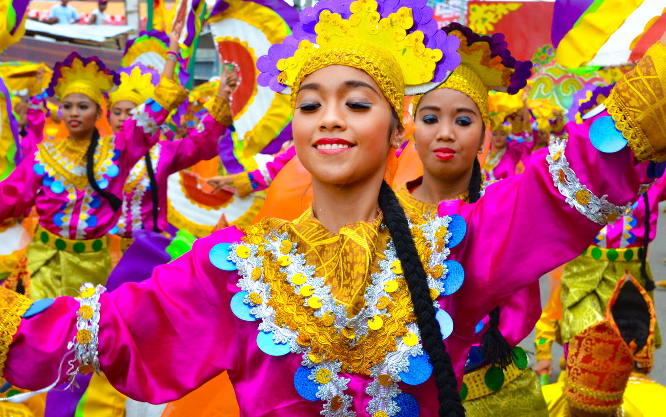 Festival dancers parade in colorful costumes and masks