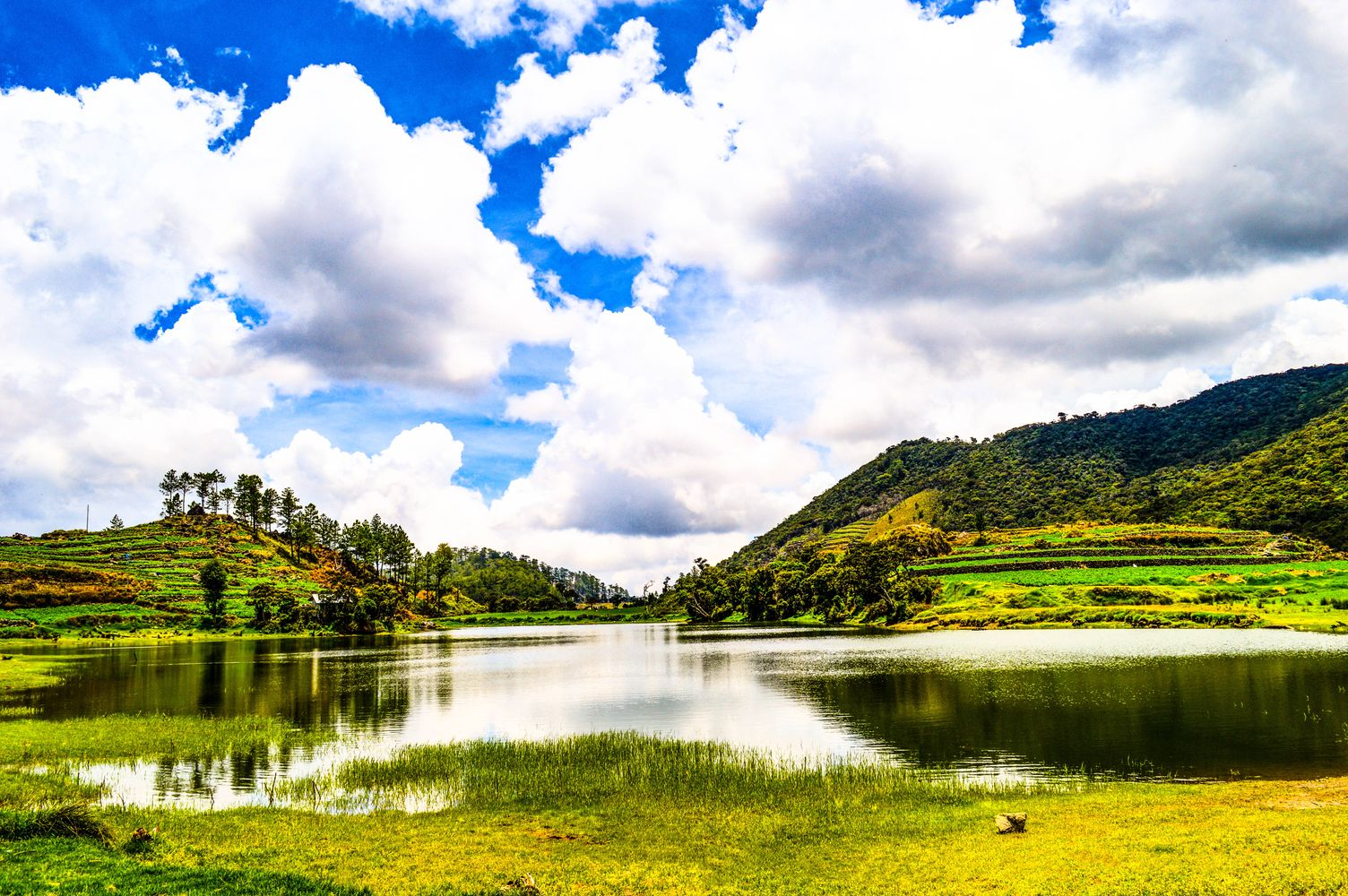 Clouds are reflected on a lake in the midst of a grassy field in Benguet, Philippines