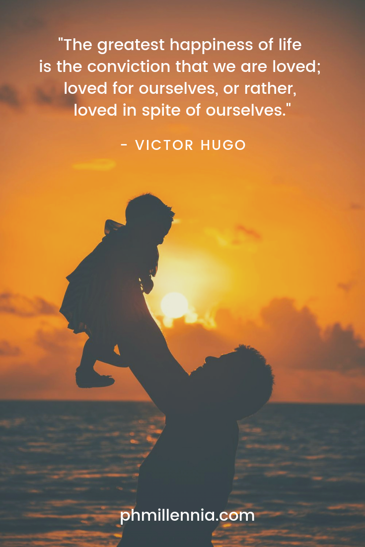 A quote on love by Victor Hugo on an image of a father holding aloft his son while being silhouetted against the setting sun.