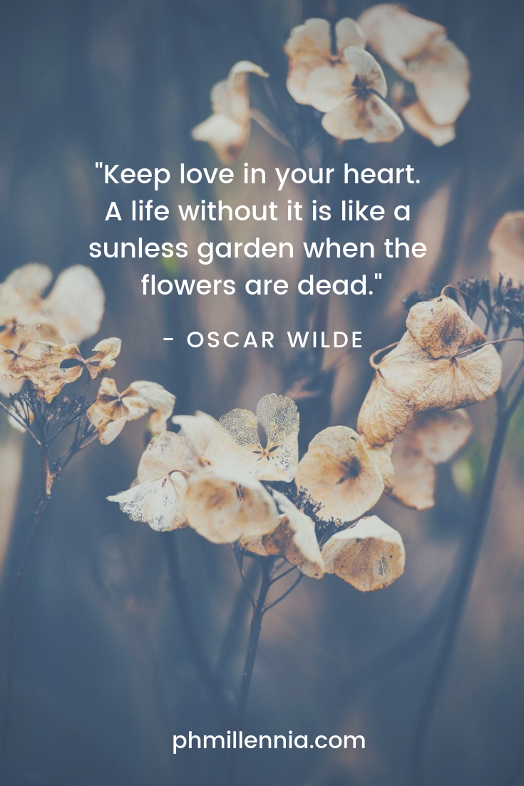 A quote on love by Oscar WIlde on an image of dead white flowers.