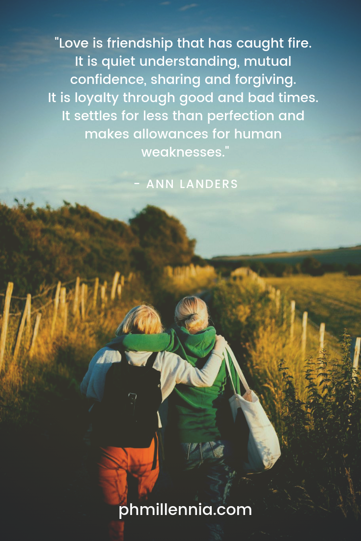 A quote on love by Ann Landers on an image of two friends walking on a dirt track through a grassy field.