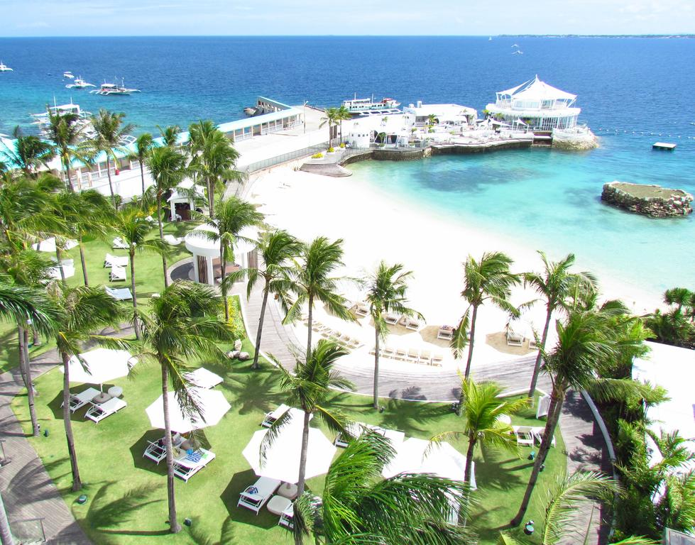 Beach resort with palm trees, white sand, clear waters in Mactan Island, Philippines