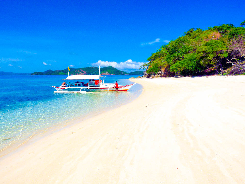 Outrigger boat moored close to white sandy shore in Coron, Philippines