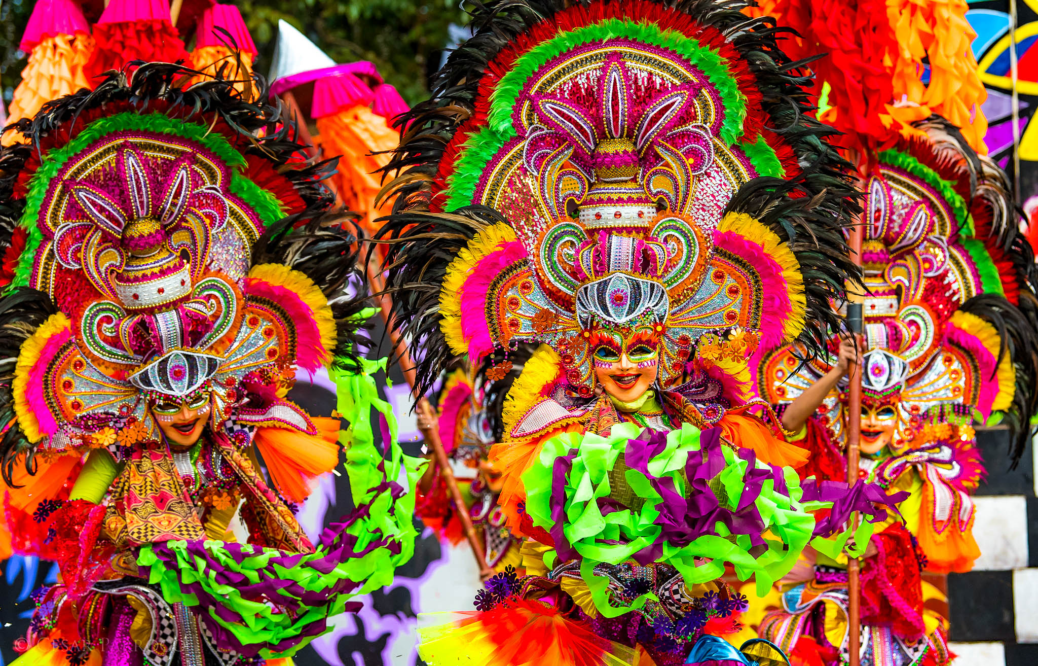 A festival parade of dancers in colorful costumes and masks