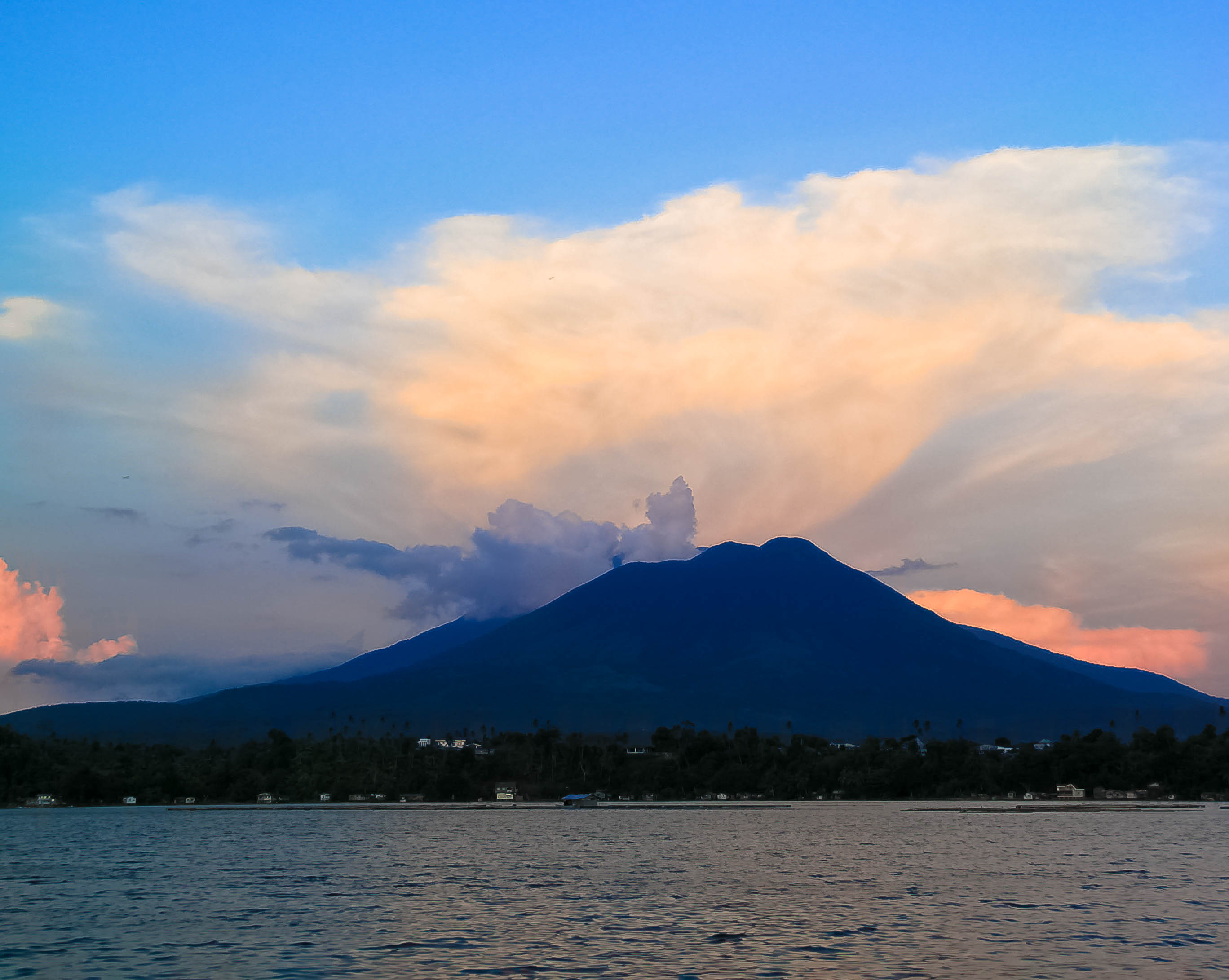 Silhouette of Mount Banahaw rising over a lake illuminated by the setting sun