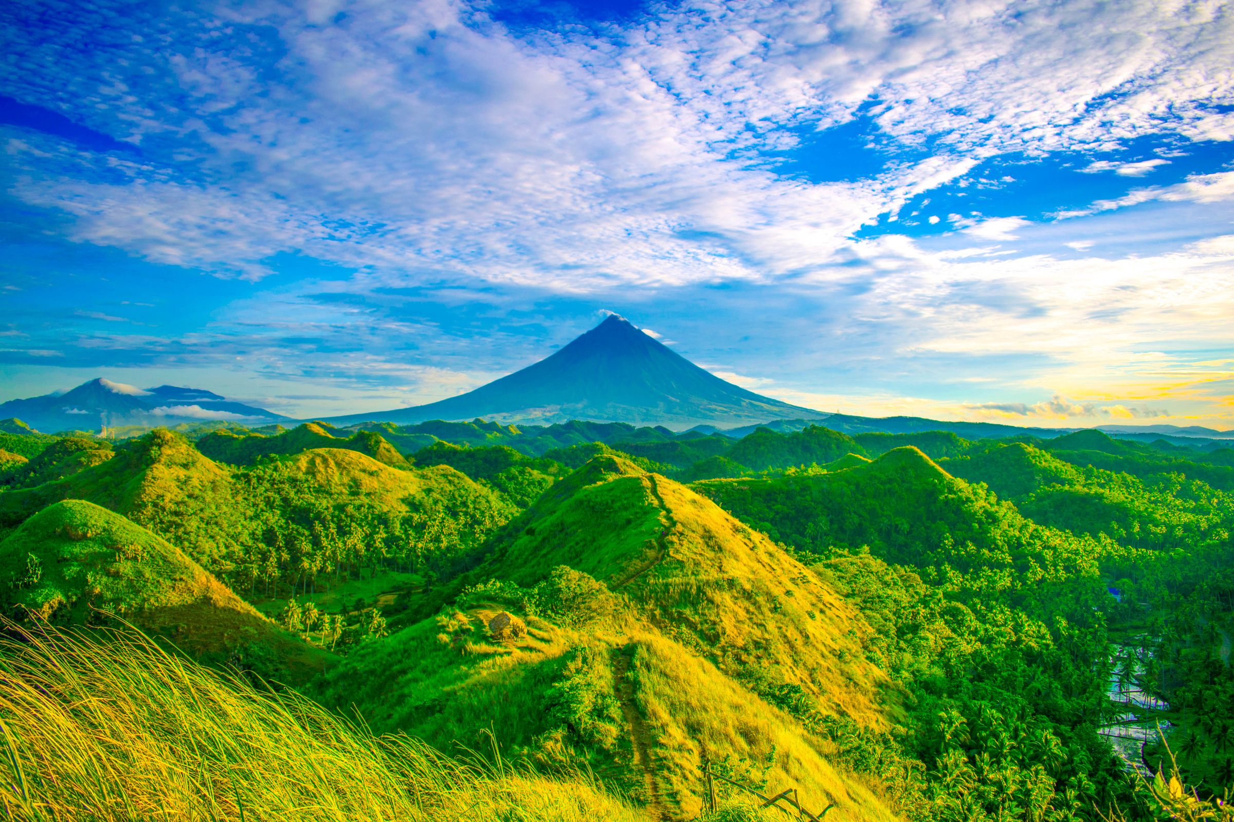 Green rolling hills of Quitinday with the perfect cone of Mount Mayon looming in the distance in Albay, Philippines