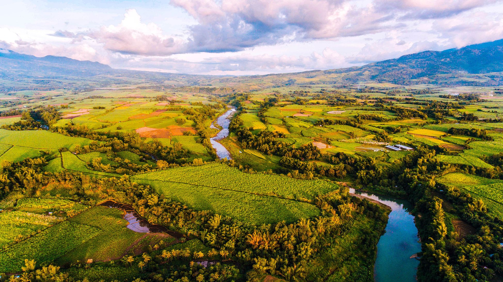 Aerial view of a river meandering through vast and verdant farms and fields with mountains looming in the distance