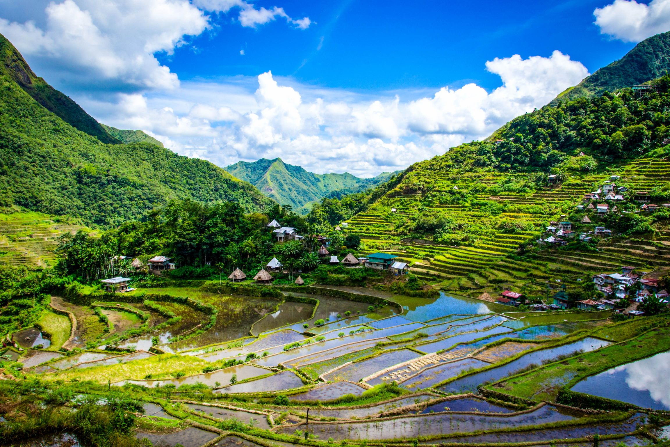 View of terraced paddy fields carved along mountainsides along with small villages in Ifugao, Philippines