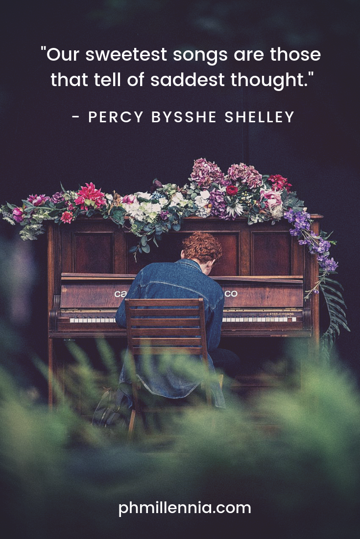 A man plays a piano wreathed with flowers
